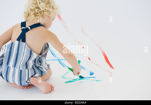Girl painting on the floor - Stock Image