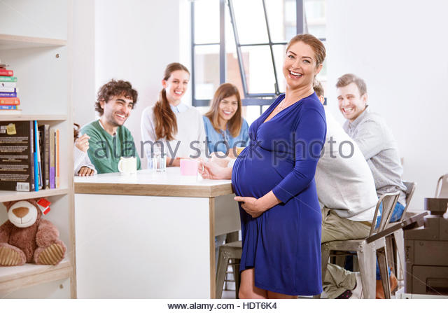 Pregnant businesswoman taking break with her co-workers. - Stock Image