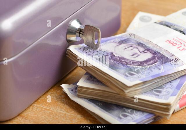 Cash box with stacks of twenty pound notes - Stock Image
