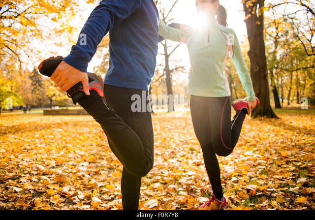 Detail of man and woman stretching legs before jogging in autumn nature - Stock-Bilder