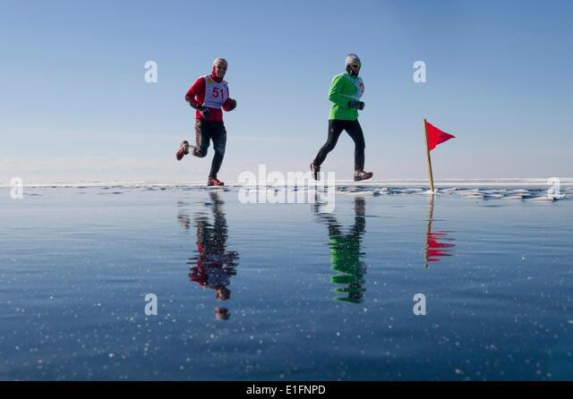 Runners in the 10th Baikal Ice Marathon, run on the frozen surface of the world's largest lake, Siberia, Irkutsk - Stock Image