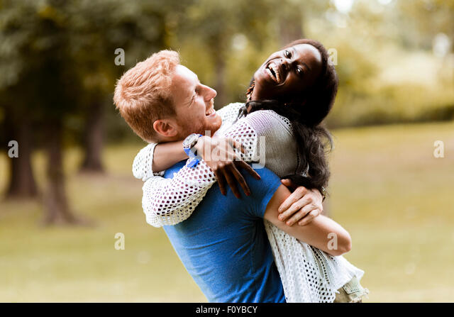 Portrait of a happy couple dancing and hugging in a park outdoors - Stock Image