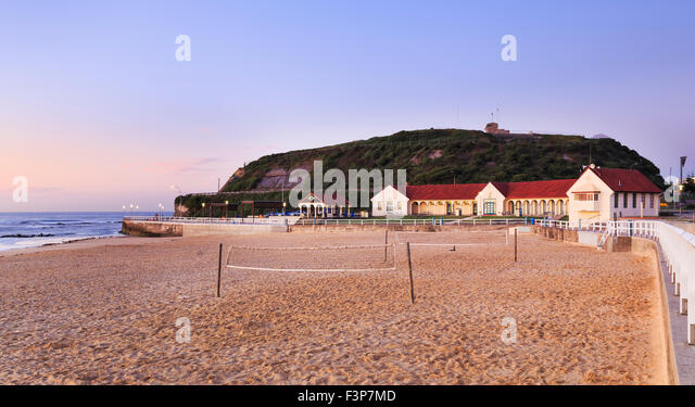 clean sandy beach in Newcastle, Australia, on Nobbys head at sunrise when nobody playing beach volleyball in front - Stock Image