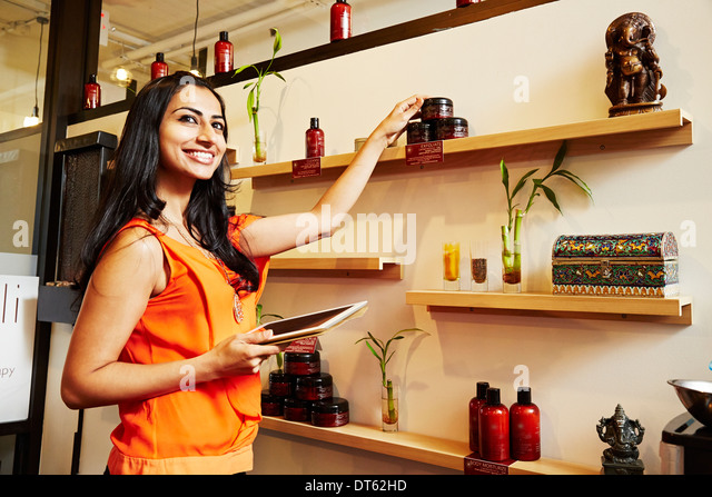 Portrait of woman touching ornaments on shelves - Stock Image