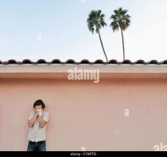 Man covering his face outdoors - Stock Image