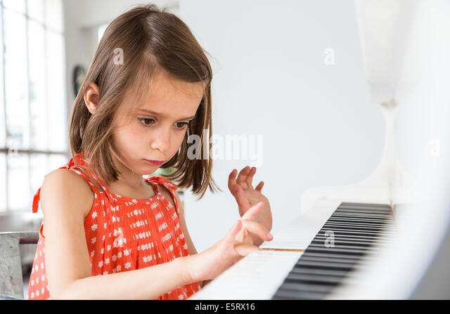 5-year-old girl playing the piano. - Stock Image