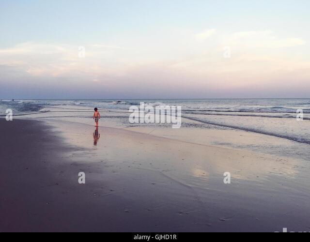 Boy walking along beach at dusk, Florida, America, USA - Stock Image