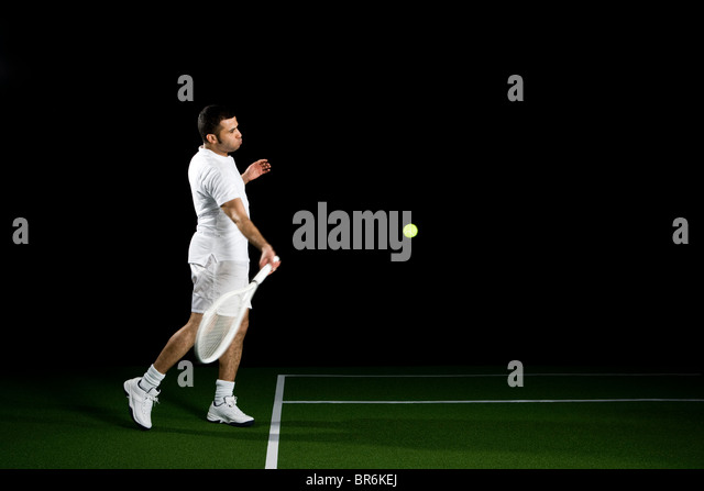 A tennis player about to a hit a ball, studio shot, portrait - Stock Image