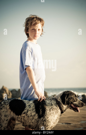 Portrait of a young boy and his dog at sunset on a quiet beach in Mexico. - Stock Image