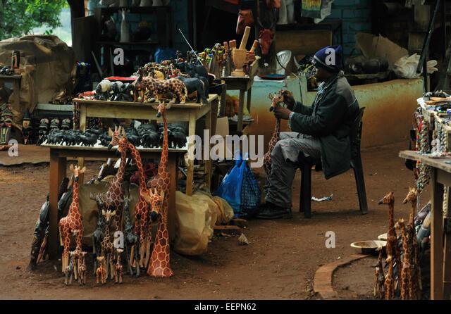 Scene of Swazi craftsman working on wooden giraffe sculpture at tourist souvenir centre Malkerns Swaziland Cultures - Stock-Bilder