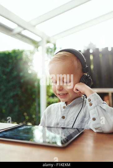 Little boy smiling in delight as he listens to music downloaded on his tablet-pc using stereo headphones while sitting - Stock-Bilder