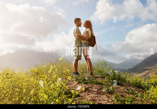 Portrait of amorous couple in embrace standing on a hill top. Young man and woman in love standing together on a - Stock Image