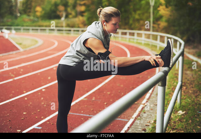 Young blonde woman stretching on track field hile listening to music - Stock Image