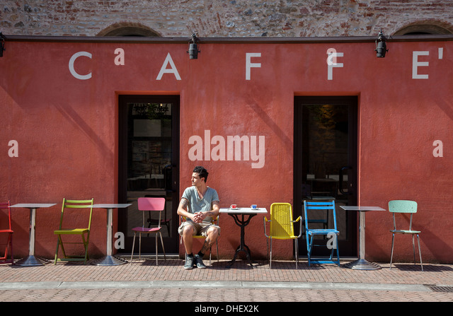 Young man sitting outside cafe, Florence, Tuscany, Italy - Stock-Bilder