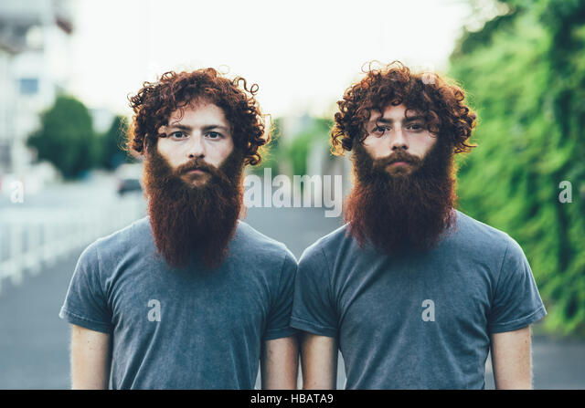 Portrait of identical adult male twins with red hair and beards on sidewalk - Stock Image