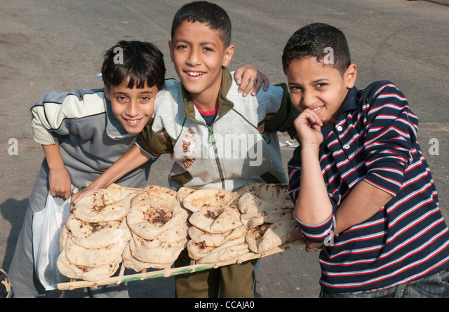 Three boys carrying a tray of fresh-baked bread, Cairo - Stock Image
