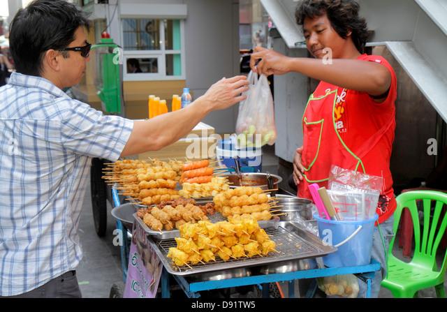 Bangkok Thailand Pathum Wan Rama 1 Road Asian man vendor street food sidewalk job preparing cook customer - Stock Image