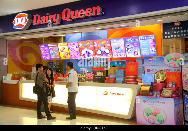 Beijing China The Malls at Oriental Plaza Dairy Queen fast food restaurant desserts menu ice cream Asian man woman - Stock Image