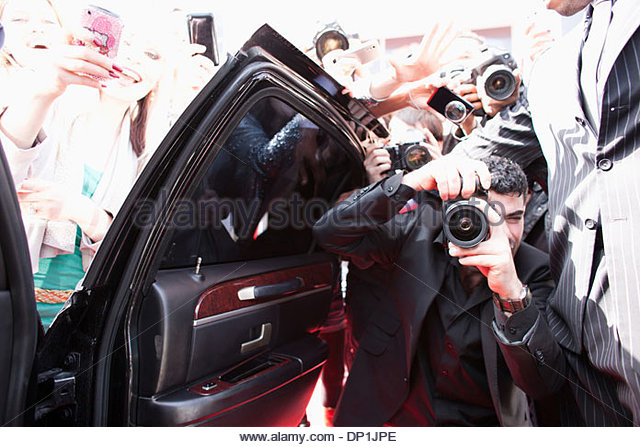 Paparazzi taking pictures of celebrity in car - Stock Image
