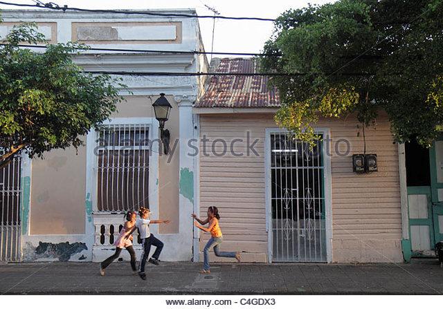 Santo Domingo Dominican Republic Ciudad Colonia Calle Portes residential street neighborhood houses Hispanic girl - Stock Image