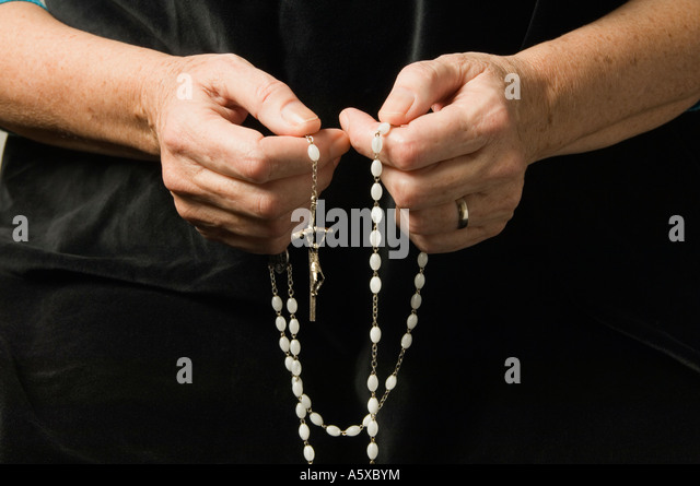 A woman's hand holding rosary beads while praying - Stock-Bilder