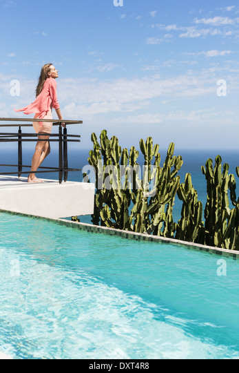 Woman basking in sun on poolside balcony overlooking ocean - Stock Image