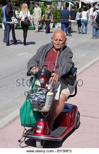 Miami Beach Florida Ocean Drive senior man electric wheelchair scooter cart oxygen disabled - Stock Image