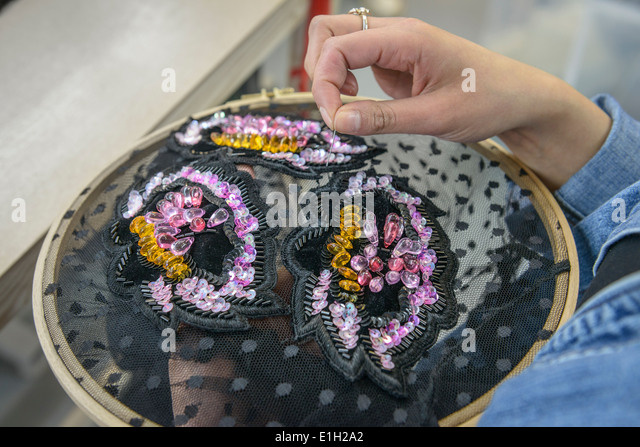 Garment worker sewing sequins in fashion studio, close up - Stock Image