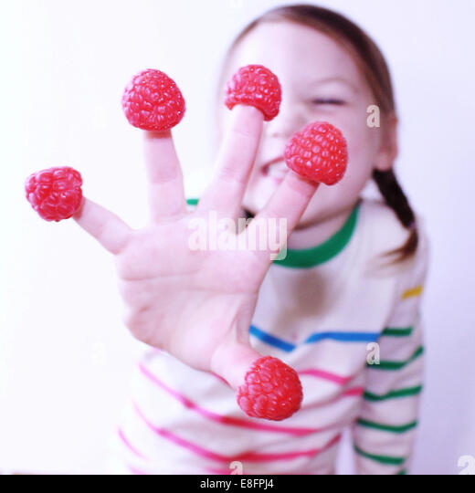 Girl with raspberries on her fingers - Stock Image