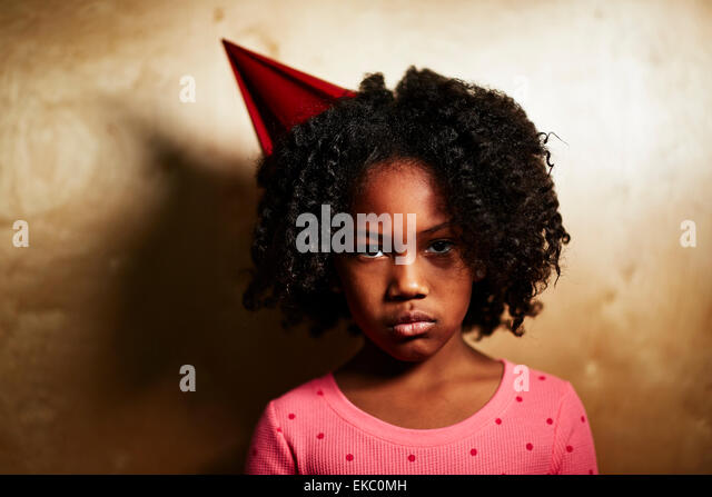 Sad girl wearing party hat - Stock Image