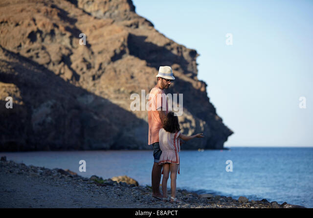 Father and daughter standing by the sea, Costa Brava, Catalonia, Spain - Stock Image