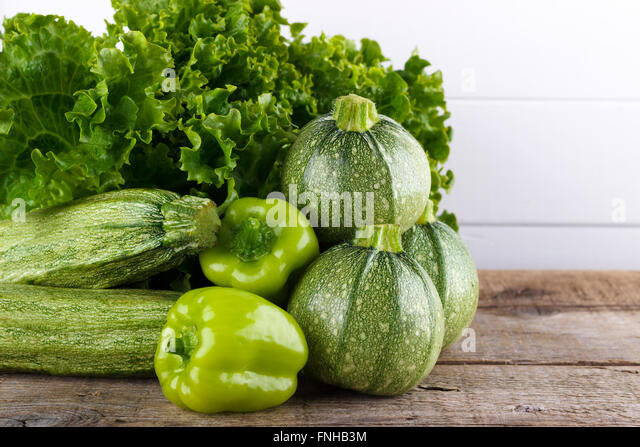 Mix of green vegetables, lettuce,bell pepper,zucchini on wooden background - Stock Image