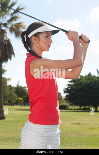 Young female playing golf - Stock Image