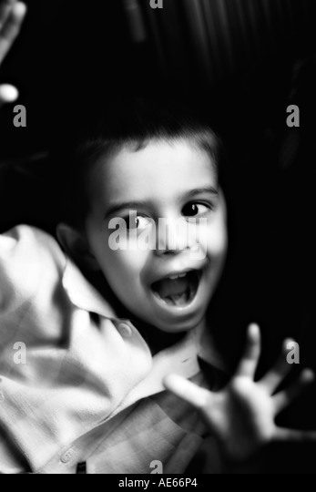 Cheeky boy with mouth open and hands raised - Stock Image
