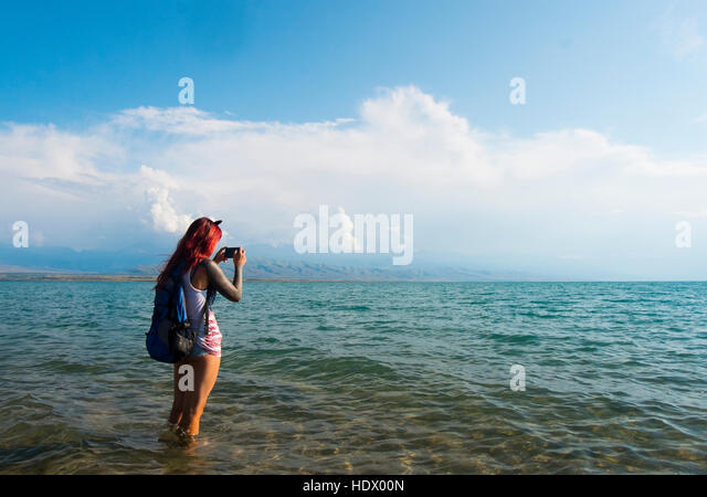 Caucasian woman wading in ocean photographing with cell phone - Stock Image