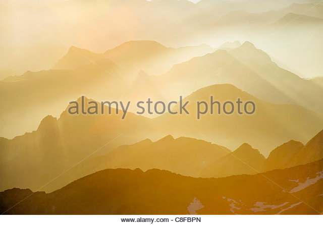 Mountains silhouetted at sunrise, view from Pico de Aneto, at 3404m the highest peak in the Pyrenees, Spain - Stock Image