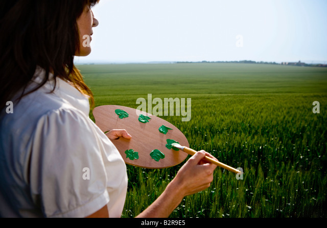 Woman holding painters palette - Stock Image