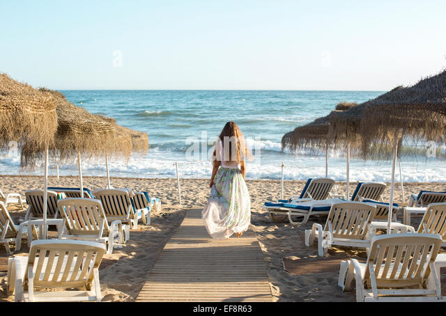 Rear view of young blond woman walking towards beach - Stock Image