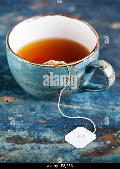 Cup of tea with teabag on blue textured background - Stock Image