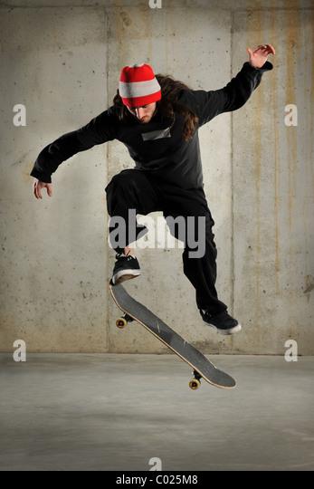 Skateboarder jumping over grunge background - Stock Image