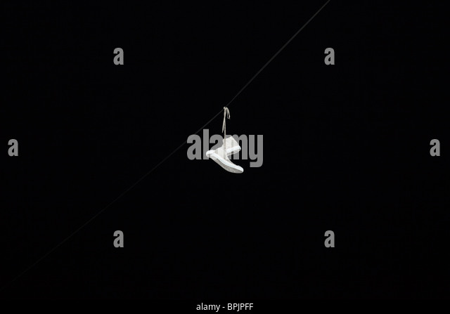 White sneakers shoes hanging by their shoelaces on a wire at night - Stock-Bilder