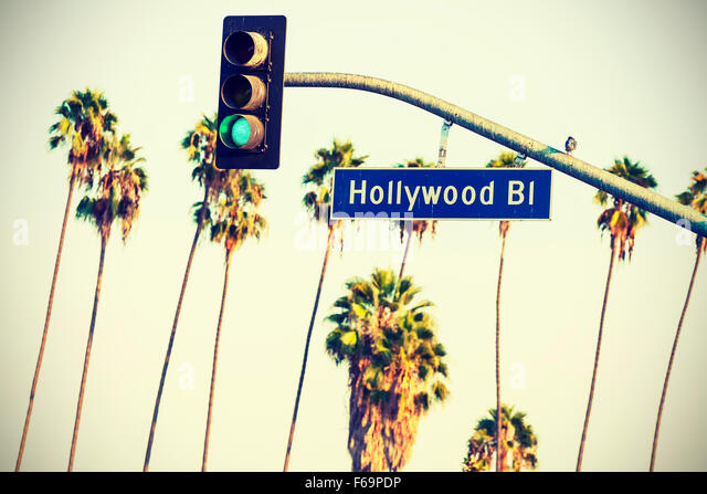 Cross processed Hollywood boulevard sign and traffic lights with palm trees in the background, Los Angeles, USA. - Stock-Bilder