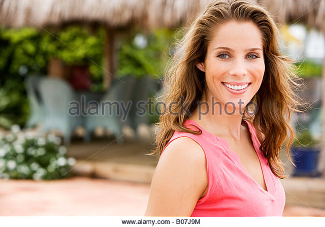 Portrait of woman outdoors at a tropical holiday resort - Stock Image