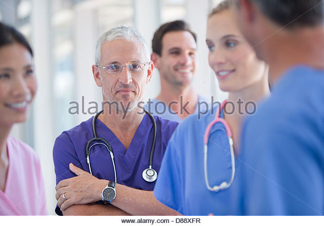 Portrait of confident doctor among co-workers - Stock Image