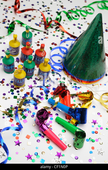 A still life image of colourful confetti, horn blowers, streamers, party hats and party poppers on white background - Stock Image