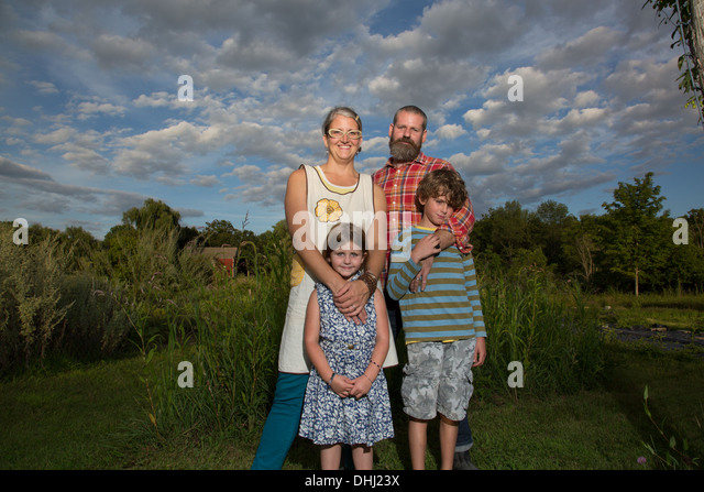 Portrait of couple with children on family herb farm - Stock-Bilder
