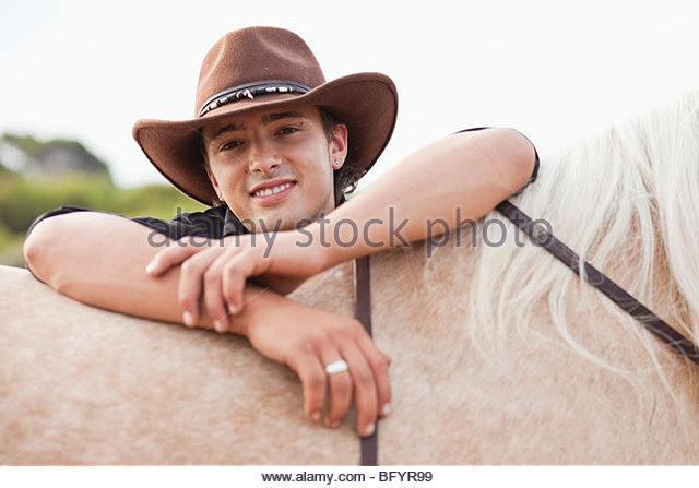 man resting on horse smiling - Stock Image