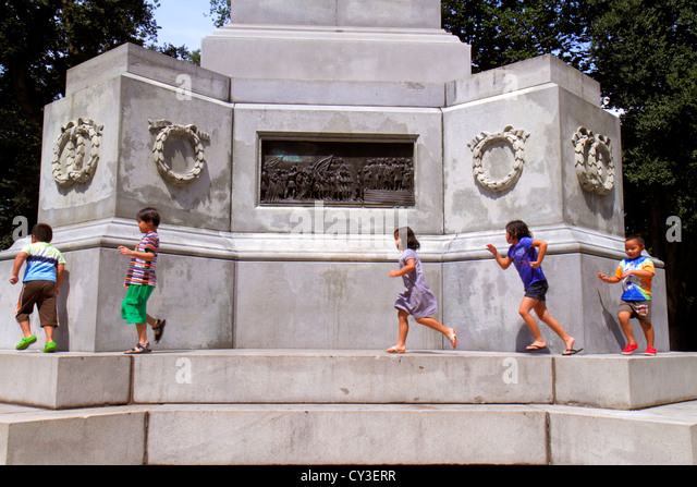 Boston Massachusetts Boston Common public park Soldiers and & Sailors Monument memorial Hispanic boy girl running - Stock Image