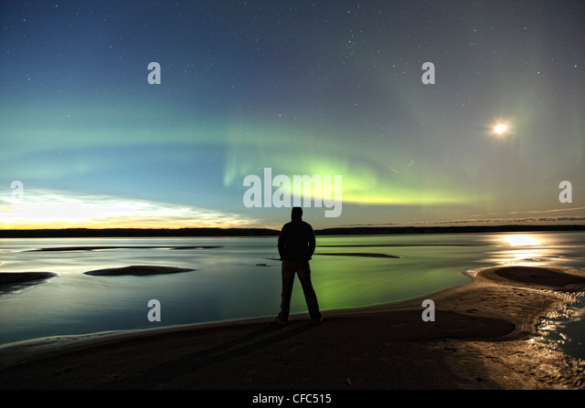 Person standing along the shores of the MacKenzie River with the aurora borealis overhead, Northwest Territories, - Stock Image