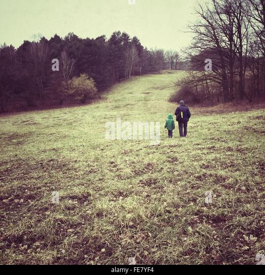Full Length Rear View Of Father With Child Standing On Grassy Field - Stock-Bilder